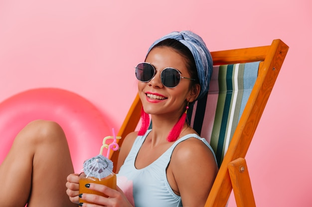 Femme élégante à lunettes de soleil, boire un cocktail