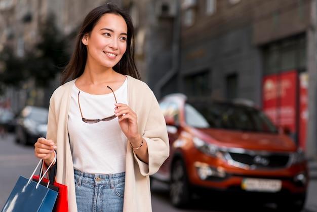 Femme élégante avec des lunettes de soleil posant à l'extérieur avec des sacs à provisions