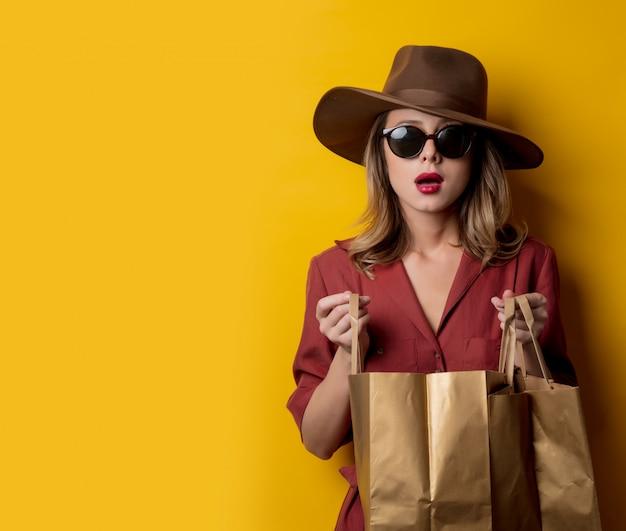 Femme élégante à lunettes de soleil et avec des sacs