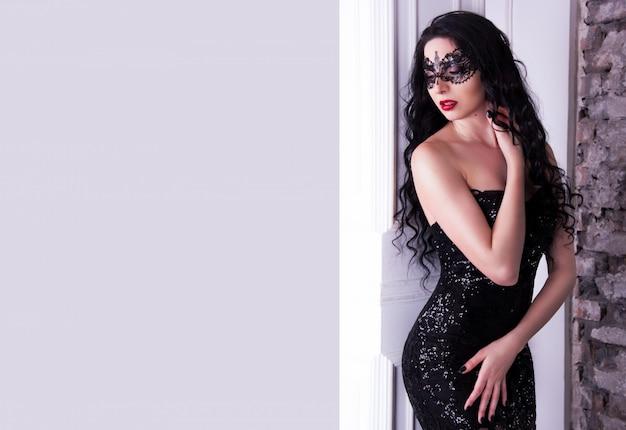 Femme élégante avec masque et robe noire
