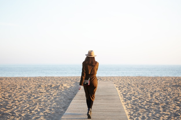 Femme élégante méconnaissable portant chapeau, long manteau et sac à bandoulière marchant le long de la promenade