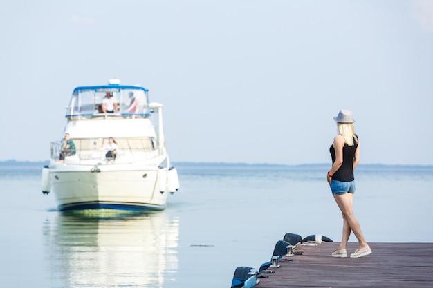 Femme élégante à la mode européenne reste au yacht club