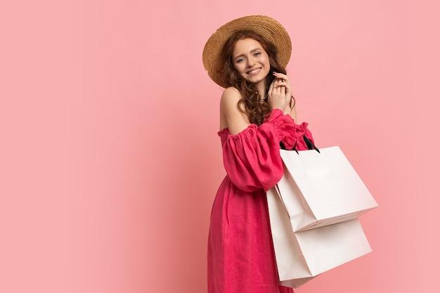 Femme élégante à la mode se réjouissant des ventes, du temps de shopping, isolée sur du rose portant une tenue décontractée.