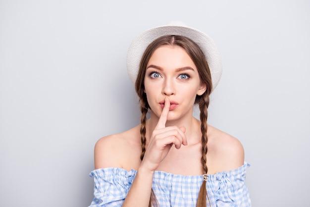 Femme élégante avec des nattes et un chapeau posant contre le mur blanc