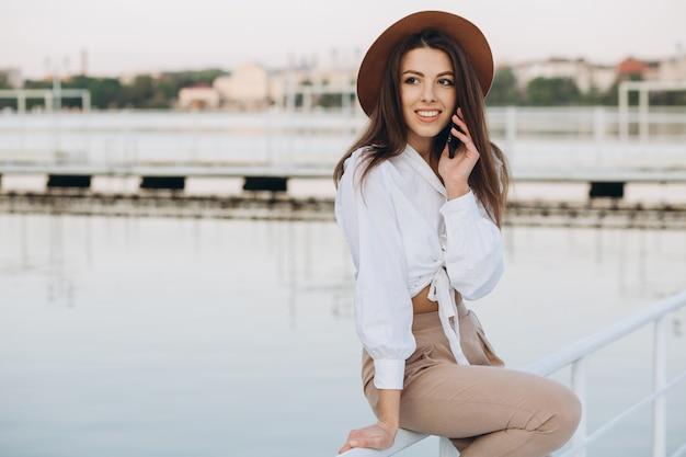 Une femme élégante, parlant par téléphone et marchant le long du front de mer sur une chaude journée d'été au coucher du soleil