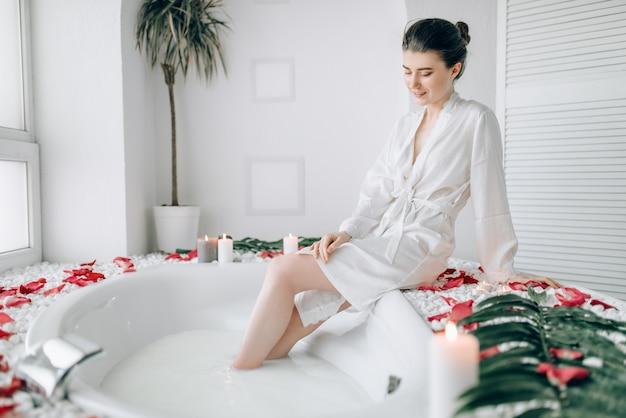 Femme élégante en peignoir blanc assis sur le bord de la baignoire décorée de pétales de rose.