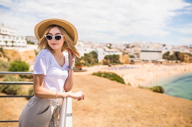 Femme élégante à la plage d'été dans une chaude journée en chapeau d'été et lunettes de soleil