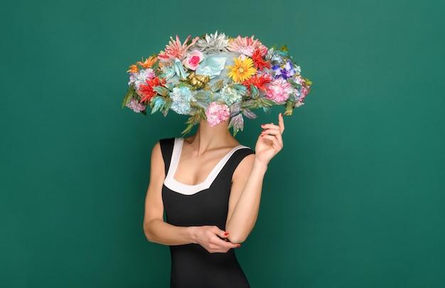 Femme élégante portant un chapeau floral à larges bords orné de fleurs d'été colorées et d'un haut noir sans manches posant sur un fond vert studio