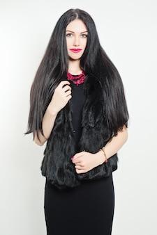 Femme élégante portant une robe noire et une veste en fourrure