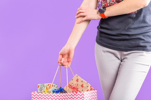 Femme élégante portant un sac en papier avec des coffrets cadeaux emballés contre du papier peint violet