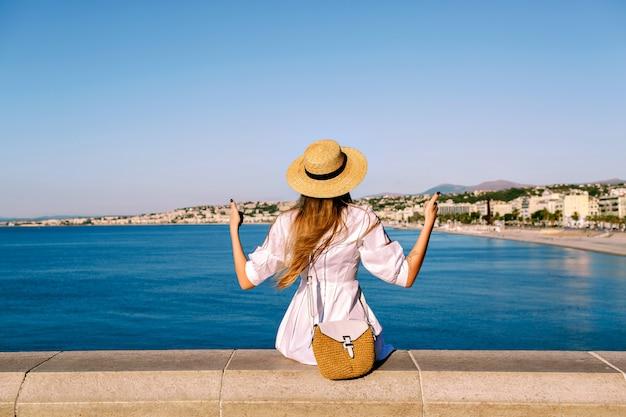 Femme élégante posant devant une vue imprenable sur nice