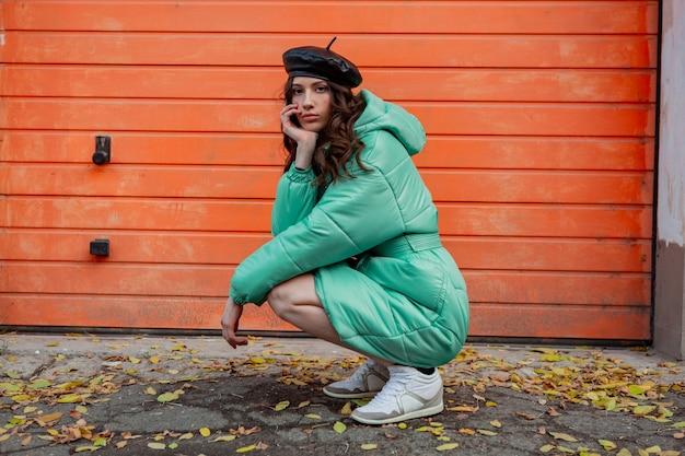 Femme élégante posant en hiver automne mode manteau matelassé et béret chapeau contre le mur orange dans la rue portant des baskets