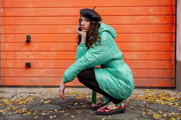 Femme élégante posant en hiver automne mode manteau matelassé et béret chapeau contre le mur orange dans la rue portant des chaussures imprimées colorées