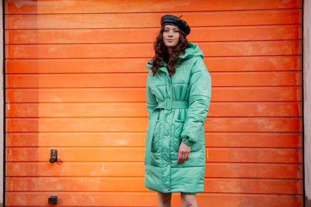 Femme élégante posant en hiver automne mode manteau matelassé et béret chapeau contre le mur orange dans la rue