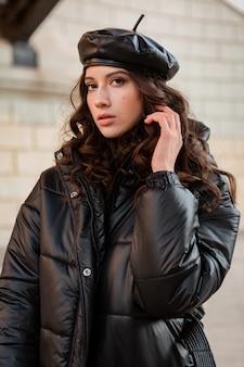 Femme élégante posant en hiver tendance de la mode automne manteau matelassé noir et béret chapeau en cuir dans la vieille belle rue portant des chaussures à talons hauts