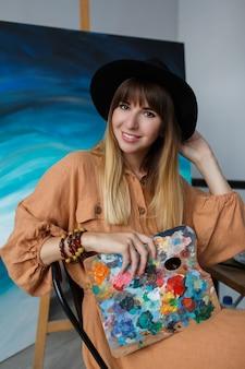 Femme élégante posant avec de nouvelles œuvres d'art.