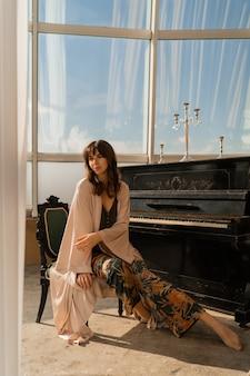 Femme élégante posant près du piano dans une pièce lumineuse élégante.