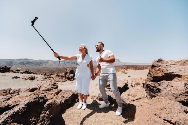 Une femme élégante prend un selfie dans le cratère du volcan teide. paysage désertique à ténérife. parc national du teide. cratère désertique du volcan teide. ténérife, îles canaries.