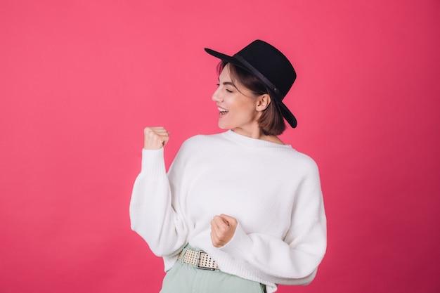 Femme élégante en pull décontracté blanc et chapeau sur un mur rose rouge