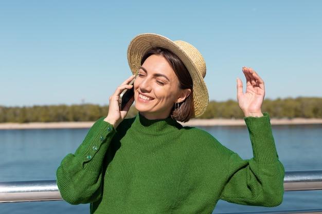 Femme élégante en pull décontracté vert et chapeau en plein air sur le pont avec vue sur la rivière à la journée d'été chaude et ensoleillée parle sur téléphone mobile