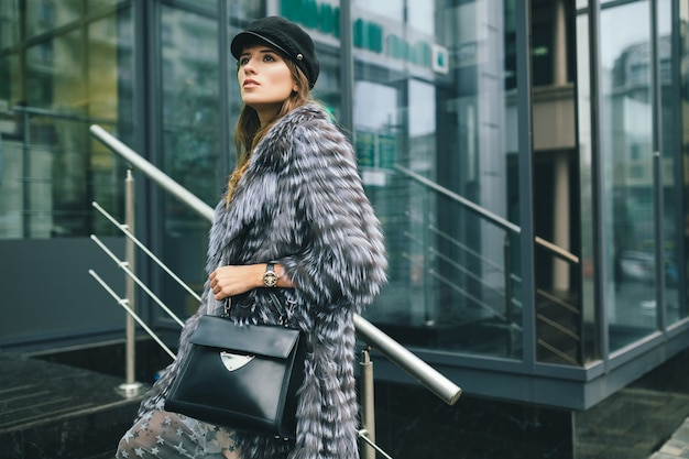 Femme élégante qui marche dans la ville en manteau de fourrure chaud, saison d'hiver, temps froid, portant une casquette noire, tenant un sac en cuir, tendance de la mode de rue, look urbain