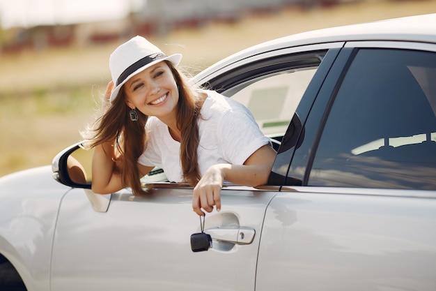 Femme élégante regarde par la fenêtre de la voiture
