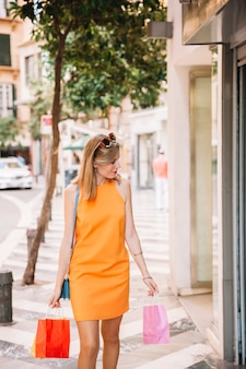 Femme élégante en robe jaune shopping