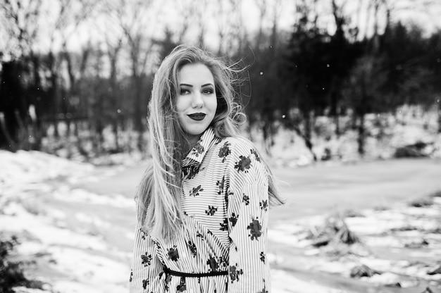 Femme élégante en robe à la journée d'hiver contre le lac gelé.