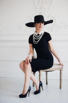 Femme élégante en robe noire avec un chapeau assis sur une chaise