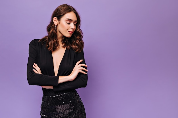 Une femme élégante en robe noire regarde vers le bas et sourit sur un mur violet