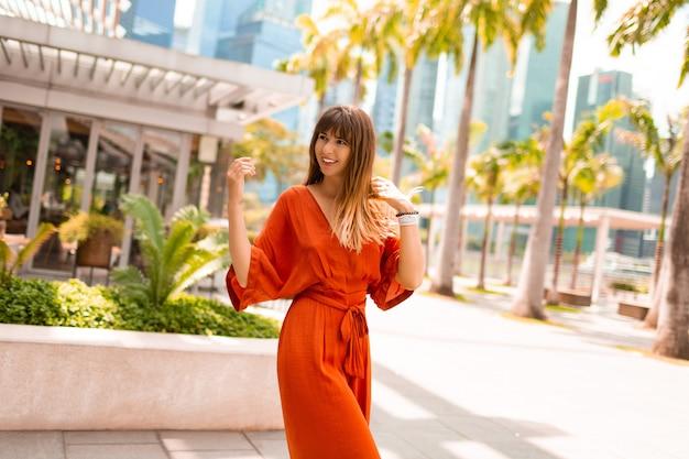 Femme élégante en robe orange posant sur la promenade avec des palmiers et des gratte-ciel dans une grande ville moderne