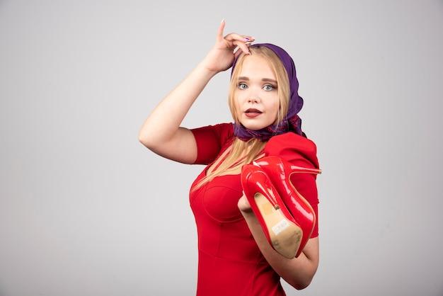 Femme élégante en robe rouge posant avec une paire de talons.