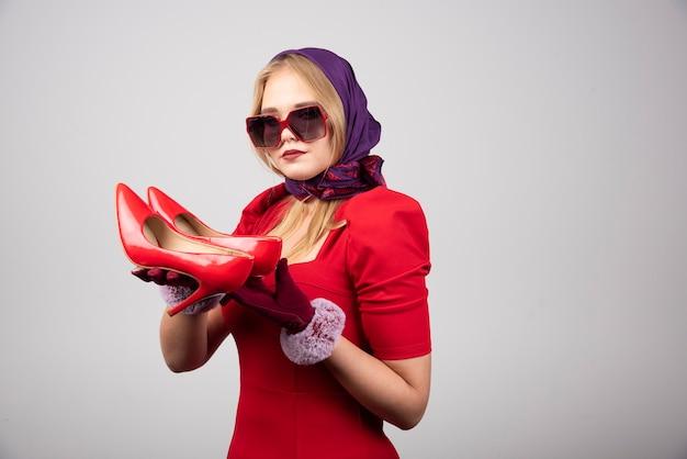 Femme élégante en robe rouge tenant une paire de talons.