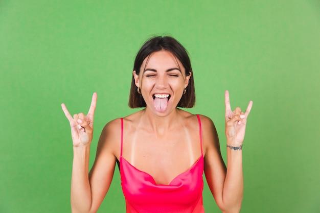 Une femme élégante en robe de soie rose isolée sur fond vert avec un geste rock montre sa langue, drôle et joyeuse