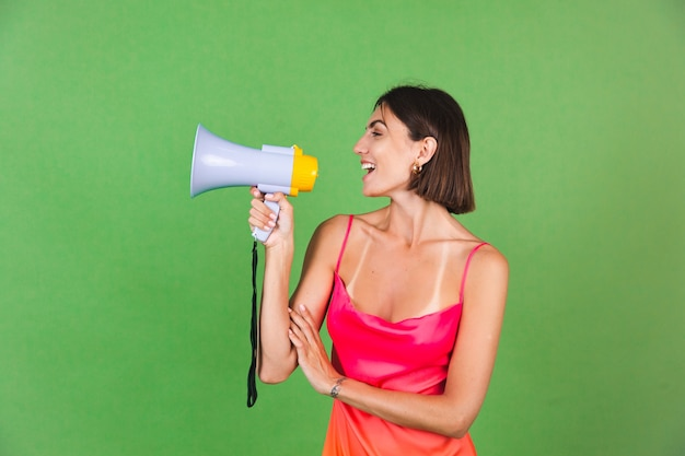 Femme élégante en robe de soie rose sur vert, joyeux excité joyeux criant joyeux dans un mégaphone, isolé