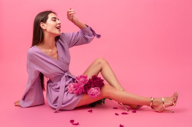 Femme élégante sur rose en été mini robe tendance violet posant avec bouquet de fleurs de pivoine assis sur le sol