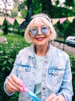 Femme élégante senior aux cheveux gris et à lunettes bleues et veste en jean soufflant des bulles en plein air