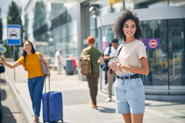 Femme élégante en short en jean et chemise avec sac à dos sur l'épaule en attente d'un taxi à l'extérieur