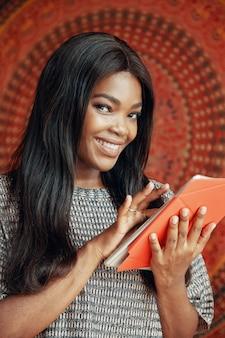 Femme élégante souriante avec tablette