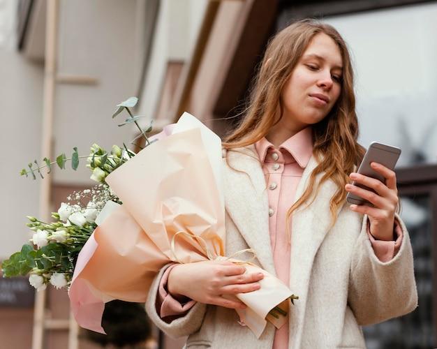 Femme élégante tenant le bouquet de fleurs à l'extérieur et à l'aide de smartphone
