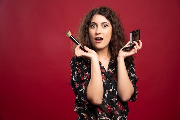 Femme élégante tenant un pinceau de maquillage et une poudre bronzante.