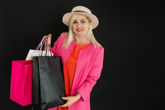 Femme élégante tenant des sacs à provisions noirs, concept de vendredi noir