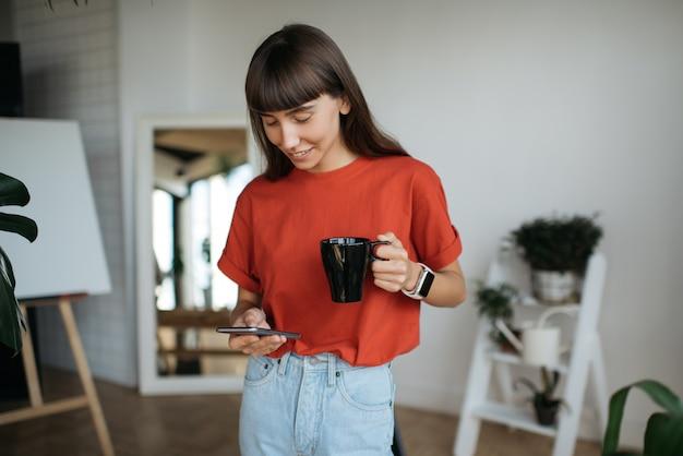 Femme élégante tenant un smartphone, une tasse de café, des achats en ligne. pigiste travaillant à domicile