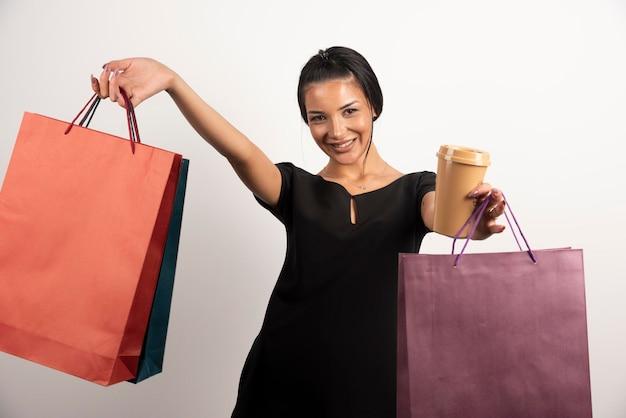 Femme élégante tenant un tas de sacs à provisions et une tasse de café.