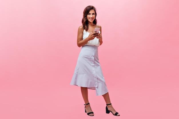 Femme élégante en tenue blanche regardant la caméra et tenant le smartphone. dame souriante en jupe longue bleu clair et haut posant sur fond rose.