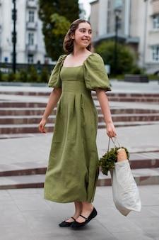 Femme élégante transportant des produits d'épicerie bio