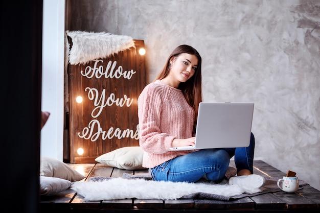 Une femme élégante travaille à la maison, étudie ou communique sur son ordinateur portable. indépendant ou étudiant travaillant en ligne.