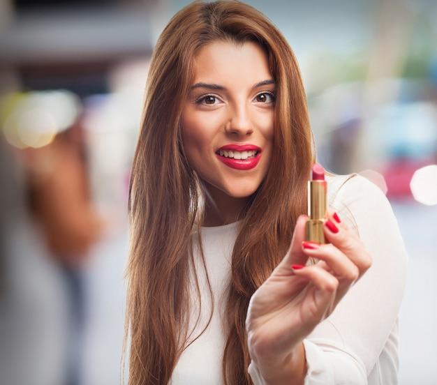 Femme élégante en utilisant un rouge à lèvres