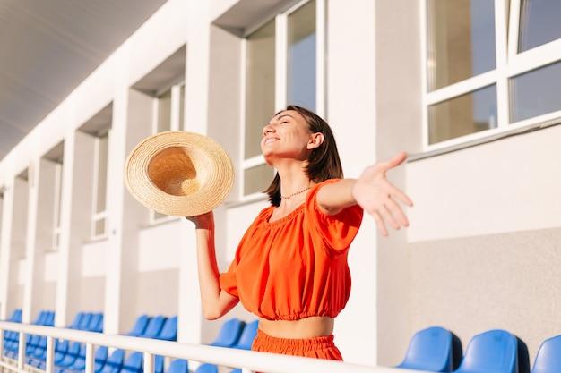 Femme élégante en vêtements orange au coucher du soleil au stade de piste cyclable posant