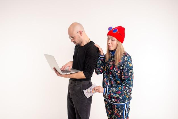 Femme élégante voler de l'argent à l'homme travaillant à l'ordinateur sur fond blanc